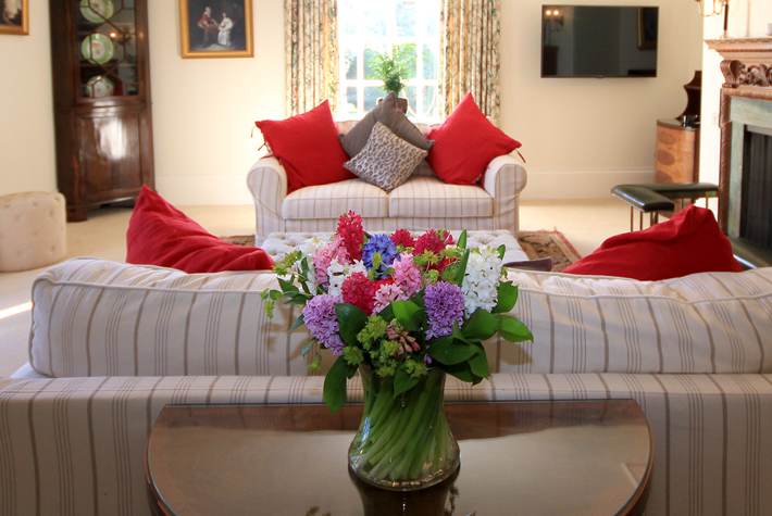 Inside the drawing room at Elsick House with fresh flowers and red cushions