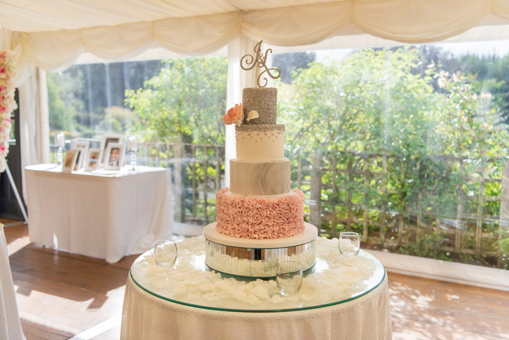 4 tier wedding cake on cake stand in marquee at Elsick House