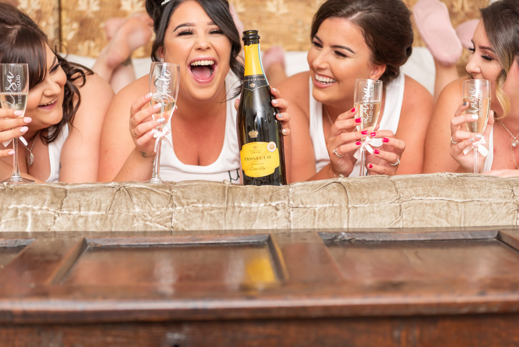 Bride and bridesmaids enjoying prosecco and laughing