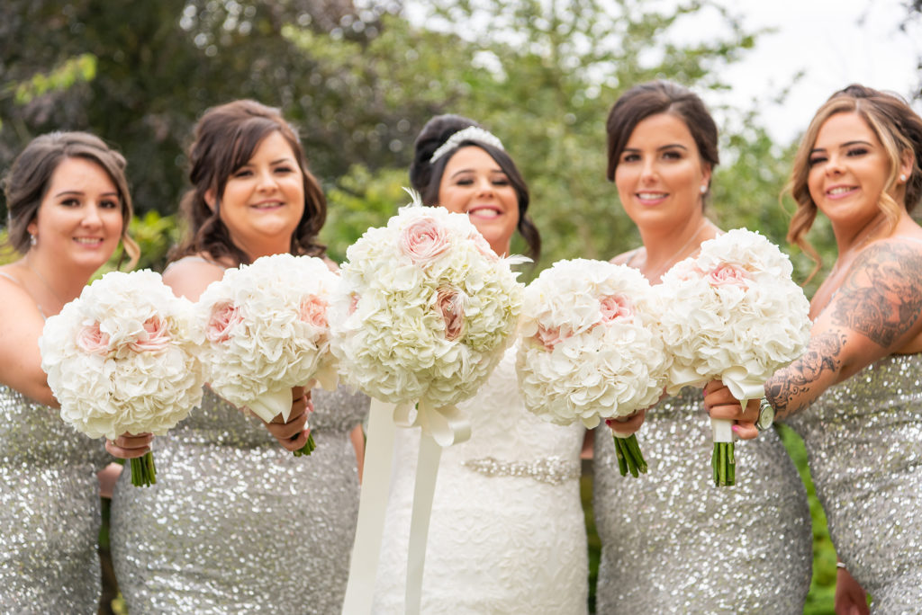 Bride and bridesmaids on wedding day with floral bouquets