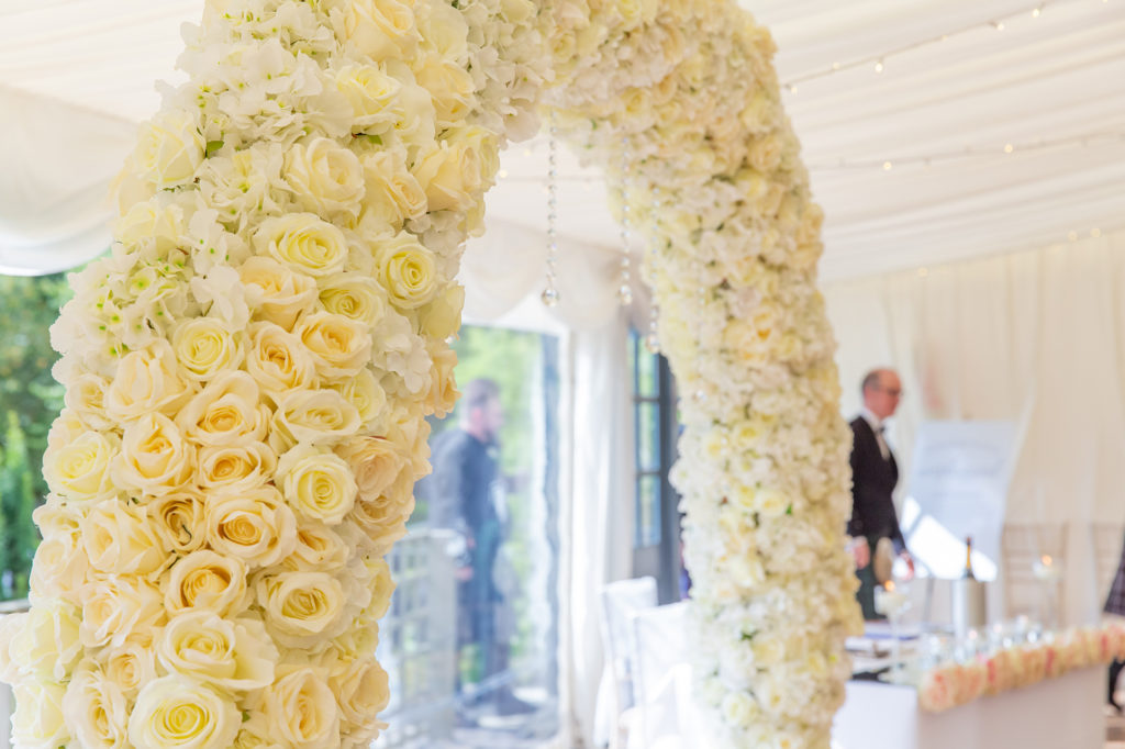 Cream floral wedding arch in ceremony in marquee at Elsick House