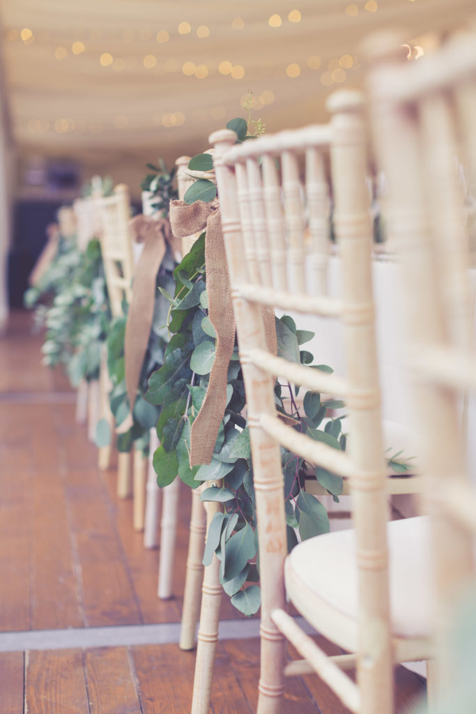 Rustic wedding chairs with hessian bows and foliage