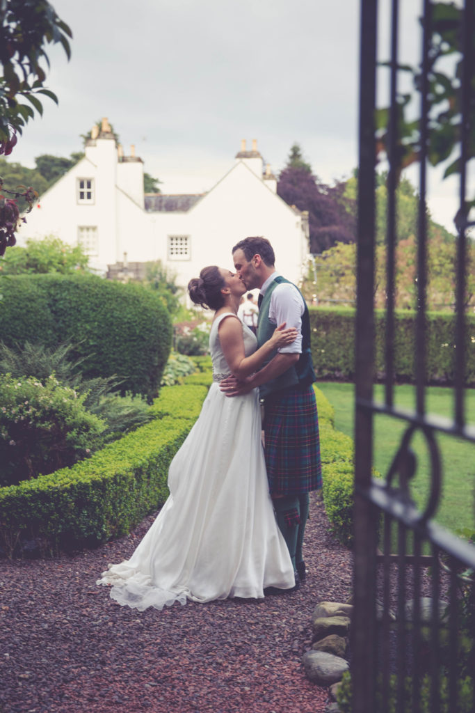 Bride and Groom, through the gate in gardens at Elsick House