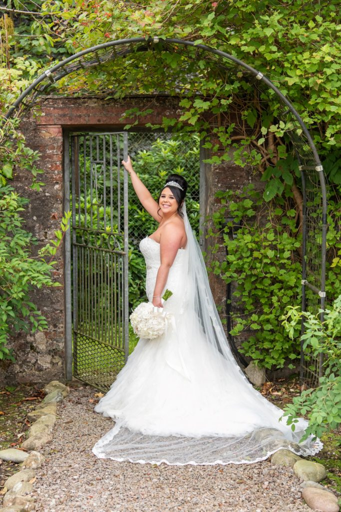 Bride Louise at the gate in the walled garden at Elsick House