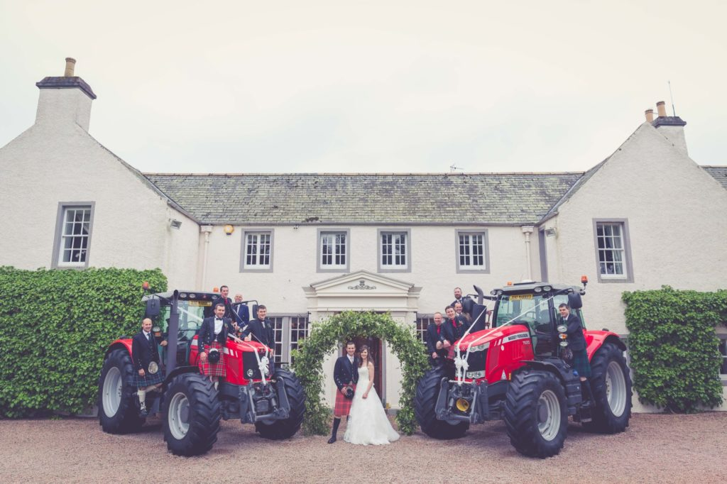 Bride and groom outside Elsick House with tractors and wedding party.