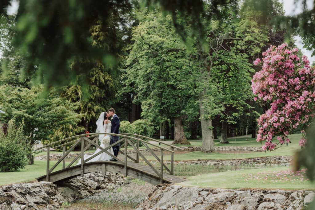 Bride and groom kissing on the bridge following wedding at Elsick House
