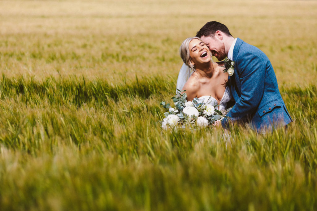 Bride and groom in fields after wedding at Elsick House