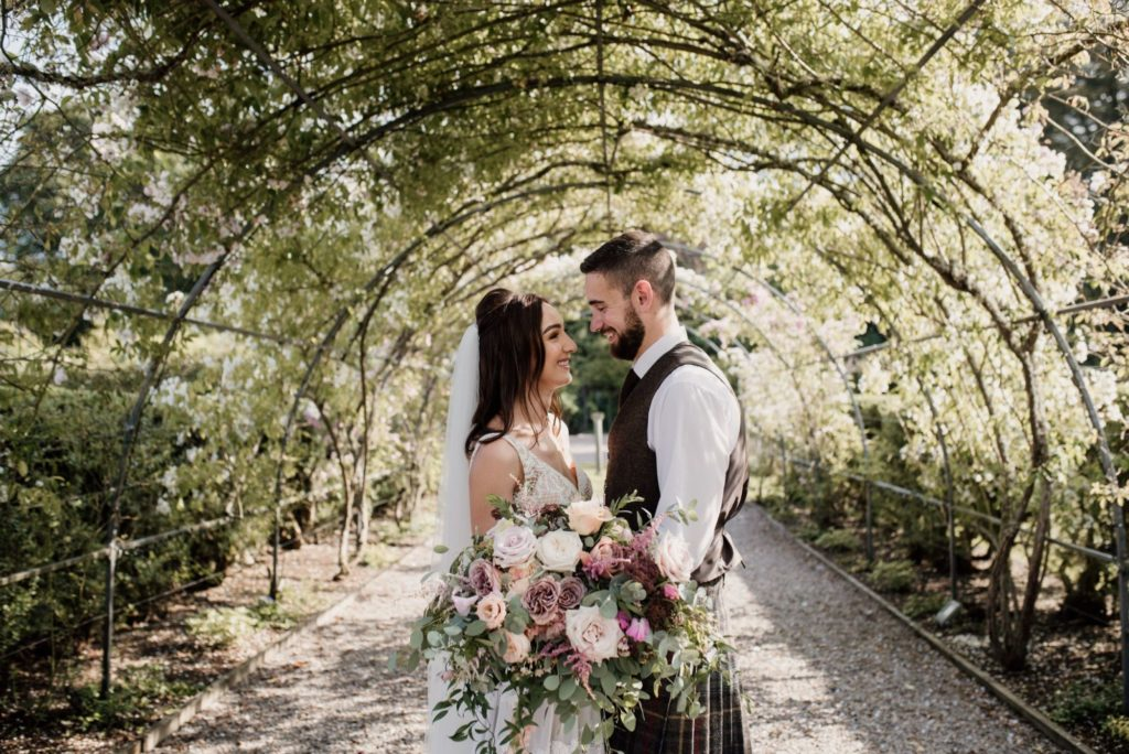 Bride and groom with floral bouquet under the rose pergola at Elsick House.