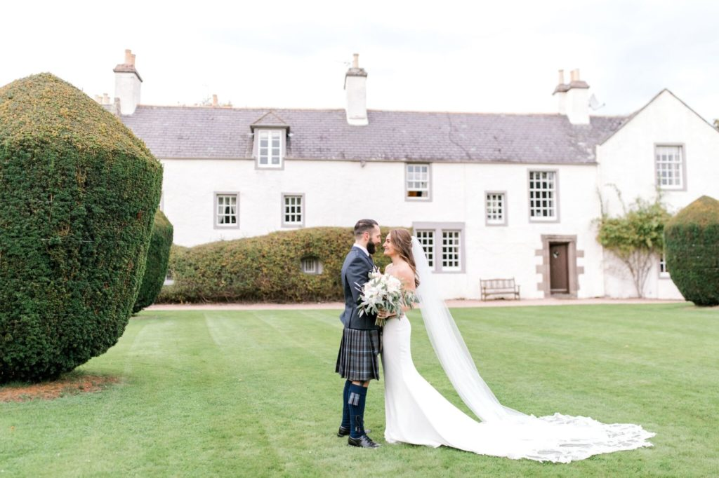 Bride and groom romantic shot on the lawn at Elsick House.