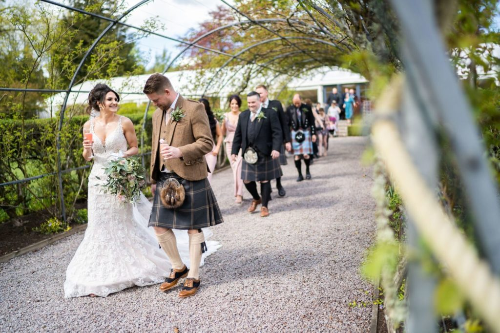 Bride and groom under the rose pergola at Elsick House.